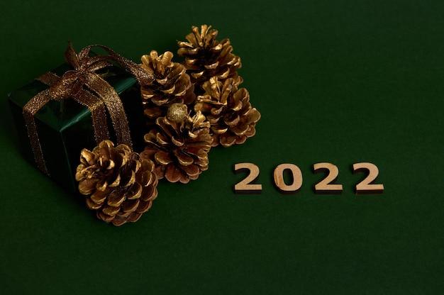 Schöne komposition aus holzziffern des jahres 2022 neben luxuriösem weihnachtsgeschenk in glänzendem grünem geschenkpapier und goldenem bogen und goldfarbenen tannenzapfen, einzeln auf dunklem hintergrund