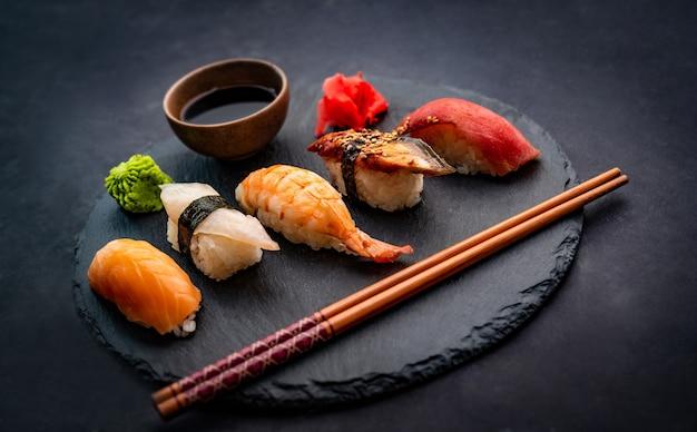 Schöne komposition aus sushi-sashimi-set mit garnelen-ingwer und sojasauce, serviert mit stäbchen ...