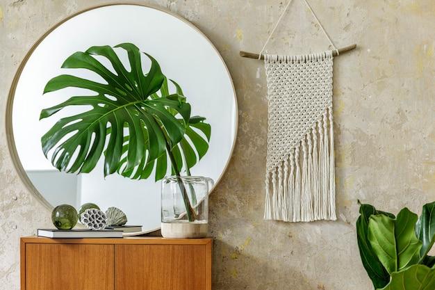 Schöne komposition im modernen retro-interieur mit design-kommode, tropischem blatt in vase, rundem spiegel, weißem makramee, buch, grunge-wand und eleganten accessoires in stilvoller wohnkultur.