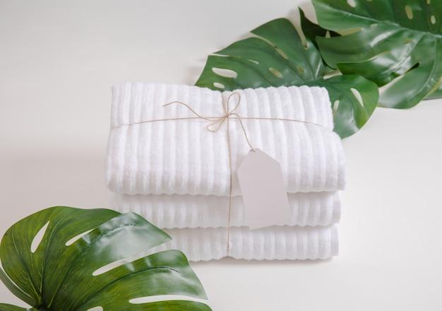 Schöne komposition mit gefalteten und gestapelten weißen frotteetüchern mit leerem etikett und monstera-blättern im tropischen stil vor weißem hintergrund