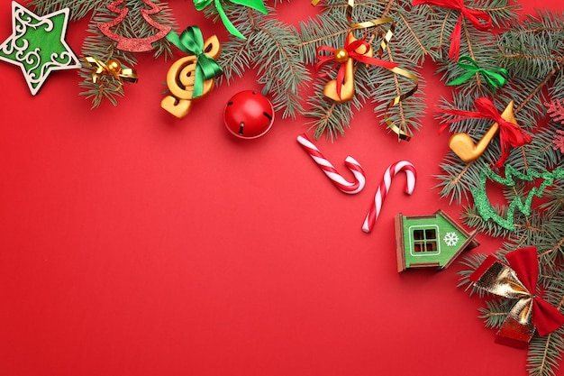 Schöne komposition mit tannenzweigen und dekorationen auf rotem hintergrund. weihnachtsmusikkonzept