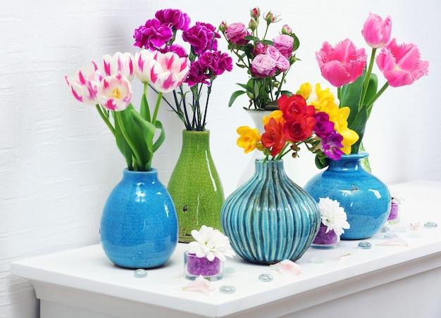 Schöne komposition mit verschiedenen blumen in vasen auf wandhintergrund