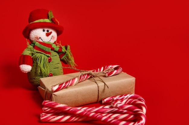 Schöne komposition von weihnachtsartikeln, geschenkbox aus kraftpapier mit gebundener schleife, süßen zuckerstangen und schneemann-plüschspielzeug einzeln auf rotem hintergrund mit kopienraum für werbung