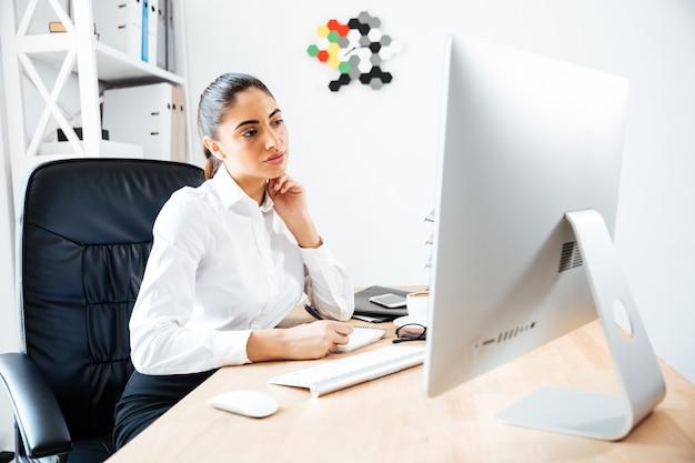 Schöne konzentrierte geschäftsfrau, die notizen macht und den computerbildschirm betrachtet, während sie im büro sitzt