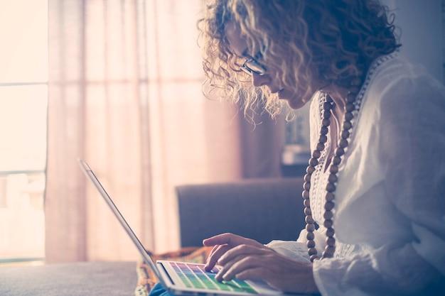 Schöne konzentrierte kaukasische frau mittleren alters, die mit farbigen stichwörtern am laptop arbeitet. schriftsteller arbeiten zu hause für alternativen lebensstil und büro. hippie und freier kleidungsfinger auf schlüsseln.