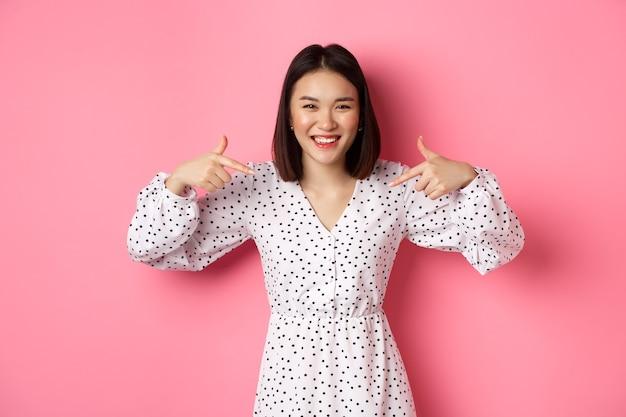Schöne koreanische frau, die mit dem finger auf ihr logo zeigt und lächelt, im kleid über romantischem rosa hintergrund stehend