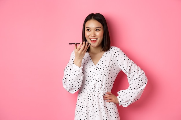Schöne koreanische frau, die über freisprecheinrichtung spricht, sprachnachrichten aufnimmt und glücklich lächelt, über rosafarbenem hintergrund stehend.