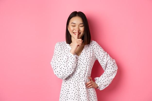 Schöne koreanische frau in trendigem kleid bittet um geheimhaltung mit sanftem lächeln und geschlossenen augen...