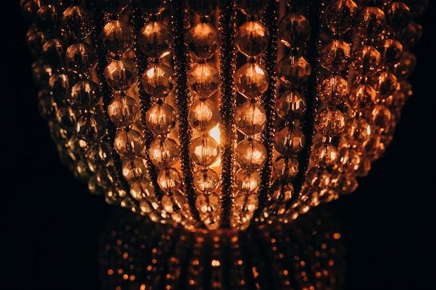 Schöne kristallleuchterlampe auf schwarzem hintergrund