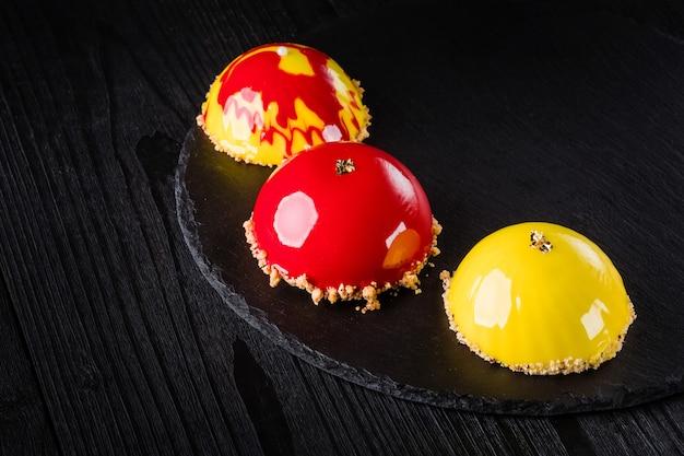 Schöne kuchen, bedeckt mit glänzend roter und gelber glasur, konzept-design-gebäck-desserts