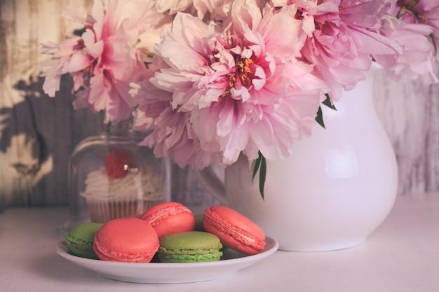 Schöne kuchen und makronen mit kaffee und blumen