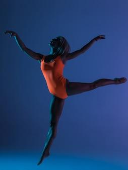 Schöne kühle junge fit turnerin frau im blauen sportswear-kleid, das ausführt, kunstgymnastikelement ausführt, springt, geteilten sprung in der luft macht, tanzt