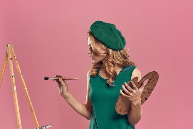 Schöne künstlerin, die das kreative hobby des pinsels der grünen baskenmützepalette trägt