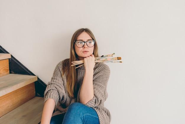Schöne künstlerin in brille und freizeitkleidung, die mit bürsten auf treppen sitzt