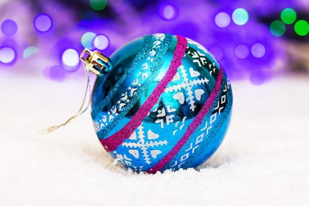 Schöne kugel für weihnachtsbaumschmuck liegt auf künstlichem schnee auf bokeh hintergrund