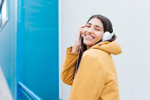 Schöne lachende frau während hörende musik