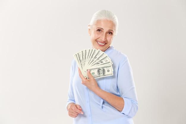 Schöne lächelnde ältere dame, die fan des geldes hält
