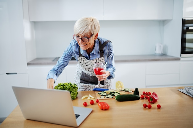 Schöne lächelnde ältere frau mit kurzen haaren und in der schürze, die glas wein hält und laptop beim stehen in der küche verwendet