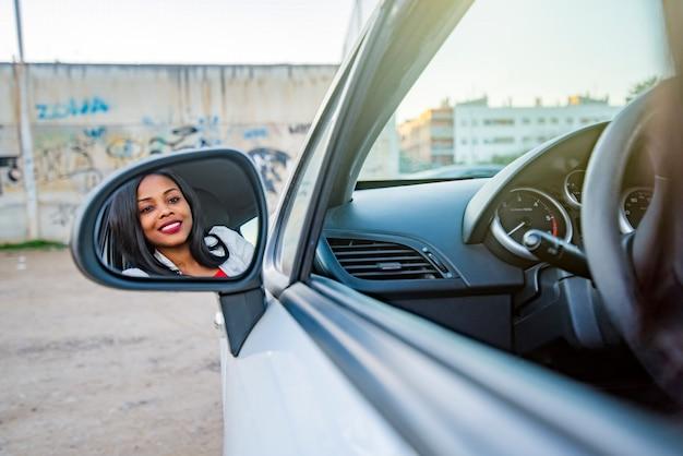 Schöne lächelnde afroamerikanische frau in einem auto, das in einem der außenspiegel reflektiert wird