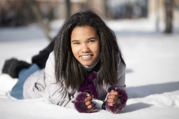 Schöne lächelnde amerikanische schwarze frau, die draußen im schnee liegt