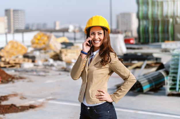 Schöne lächelnde architektin mit braunem haar, gekleidet, lässig gekleidet und mit helm auf kopf, der am telefon spricht, während sie auf der baustelle steht.