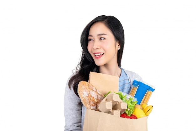 Schöne lächelnde asiatische frau, die einkaufstasche des lebensmittels hält und weg zum leeren raum beiseite lokalisiert auf weißem hintergrund schaut