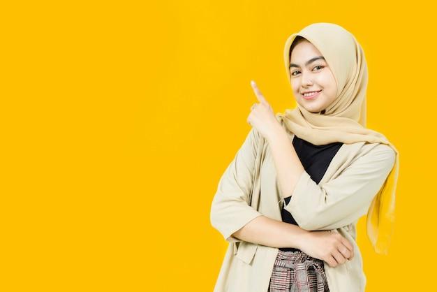 Schöne lächelnde asiatische frau, die hand auf leeren raum auf gelber wand zeigt