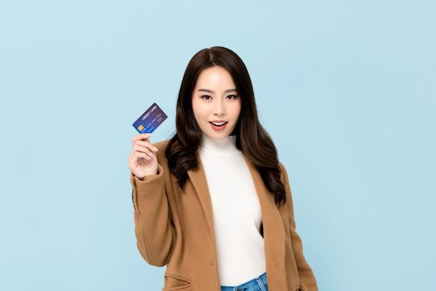 Schöne lächelnde asiatische frau, die kreditkarte in der hand zeigt