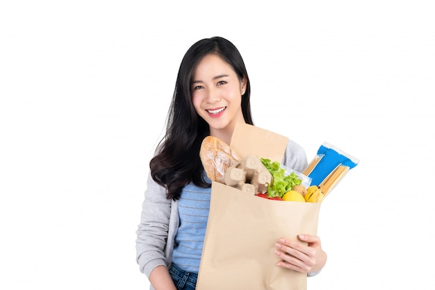 Schöne lächelnde asiatische frau, die papiereinkaufstasche voll von lebensmitteln und lebensmitteln lokalisiert auf weißem hintergrund hält