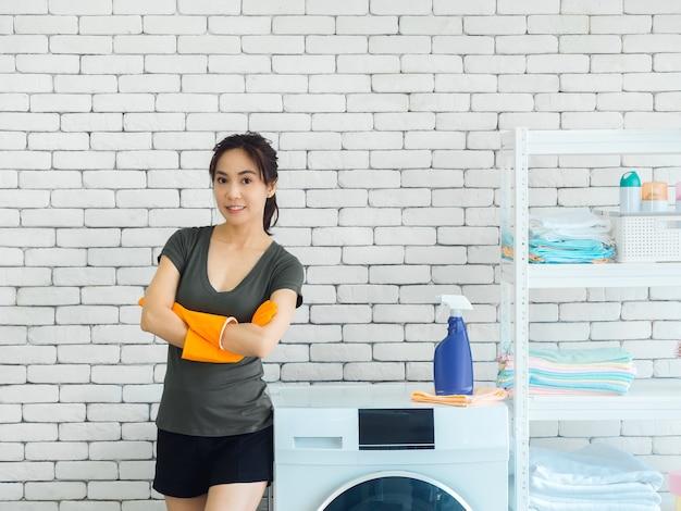 Schöne lächelnde asiatische frau, glückliche hausfrau, die orange schutzgummihandschuhe trägt, die mit den armen stehen, die neben waschmaschine auf weißer backsteinmauer gefaltet werden
