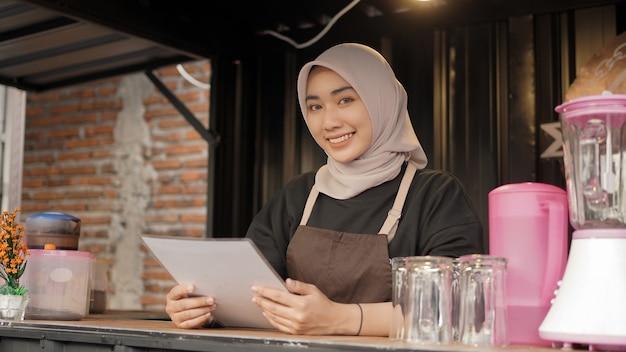 Schöne lächelnde asiatische kellnerin mit menüliste im café-standcontainer