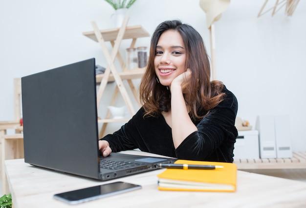 Schöne lächelnde asiatische studentenfrau, die vom on-line-bildungsservice, von der jungen asiatin tut hausarbeit mit computerlaptop, notizbuch und intelligentem telefon lernt