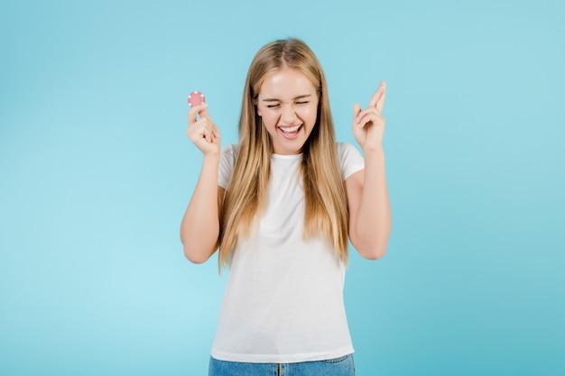 Schöne lächelnde blonde frau mit schürhakenchip vom on-line-kasino getrennt über blau
