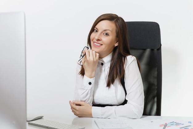 Schöne lächelnde braunhaarige geschäftsfrau in anzug und brille am schreibtisch sitzend, am computer mit modernem monitor mit dokumenten im hellen büro arbeiten working