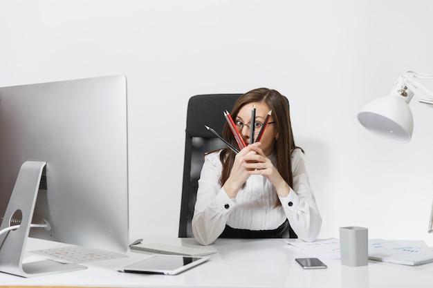 Schöne lächelnde braunhaarige geschäftsfrau in anzug und brille, die am schreibtisch sitzt, am computer mit modernem monitor mit dokumenten im hellen büro arbeitet und sich hinter bleistiften versteckt hiding