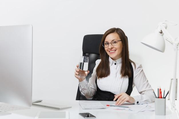 Schöne lächelnde braunhaarige geschäftsfrau in anzug und brille, die mit einem glas reinem wasser am schreibtisch sitzt und am computer mit modernem monitor mit dokumenten im hellen büro arbeitet working