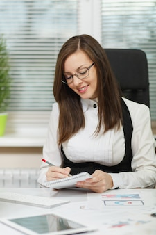 Schöne lächelnde braunhaarige geschäftsfrau in anzug und brille, die mit tablet am schreibtisch sitzt, am computer mit dokumenten im hellen büro arbeitet, mit bleistiftinformationen in das notebook schreibt writing