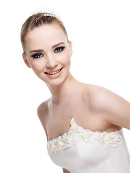 Schöne lächelnde braut, die hochzeitskleid trägt.