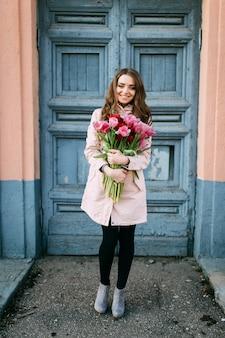 Schöne lächelnde brünette frau, die vor alter tür mit einem strauß frischer tulpen steht.