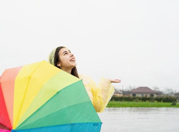 Schöne lächelnde brünette frau im gelben regenmantel, die einen regenbogenregenschirm im regen hält und regentropfen mit ihrer hand auffängt