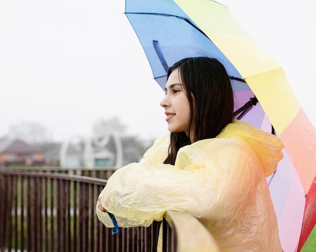 Schöne lächelnde brünette frau im gelben regenmantel, die einen regenbogenregenschirm im regen hält und wegschaut. platz kopieren