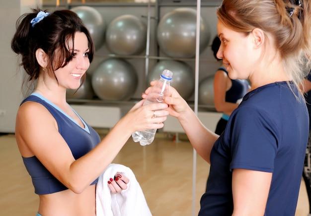 Schöne lächelnde brünette frau in sportbekleidung gibt flasche wasser zu blondem mädchen