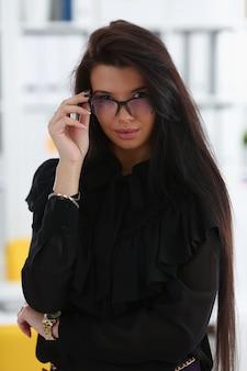Schöne lächelnde brünette frau mit brille im büro