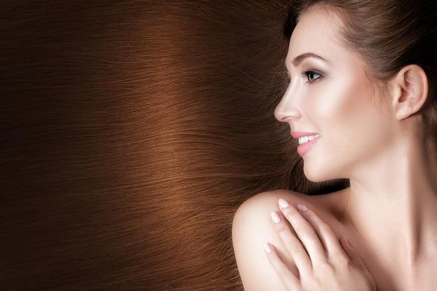 Schöne lächelnde brünette frau mit gesunden langen haaren