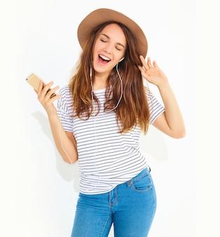 Schöne lächelnde brunettefrauenfrau im zufälligen hippiesommer kleidet ohne make-up in hörender musik des braunen hutes im telefon mit den kopfhörern, die auf weiß lokalisiert werden