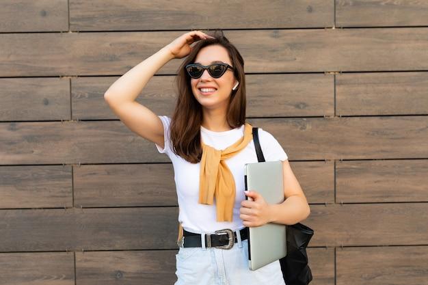 Schöne lächelnde charmante junge brunet-frau, die die kamera mit computer-laptop und sonnenbrille in weißem t-shirt und hellblauer jeans auf der straße betrachtet.