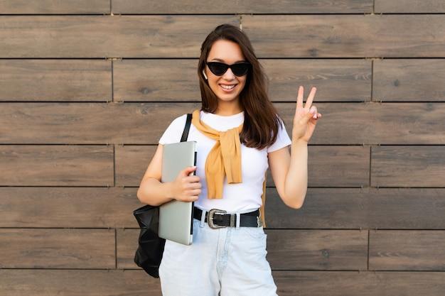 Schöne lächelnde charmante junge brunetfrau, die kamera betrachtet, die computer-laptop und hält