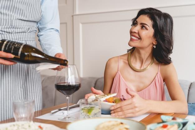 Schöne lächelnde dame, die am tisch mit leckerem essen sitzt, während die café-arbeiterin alkoholisches getränk in glas gießt?