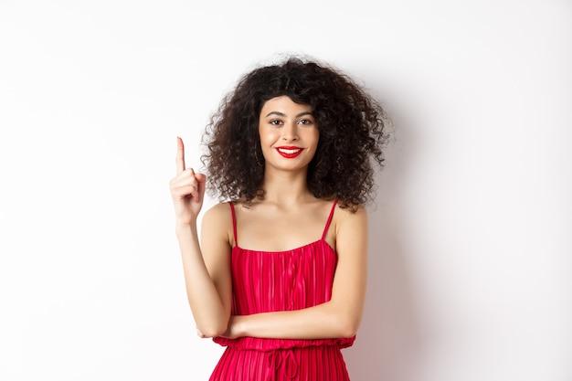 Schöne lächelnde dame im roten kleid, das nummer eins zeigt, finger hebt und erfreut schaut, über weißem hintergrund stehend.