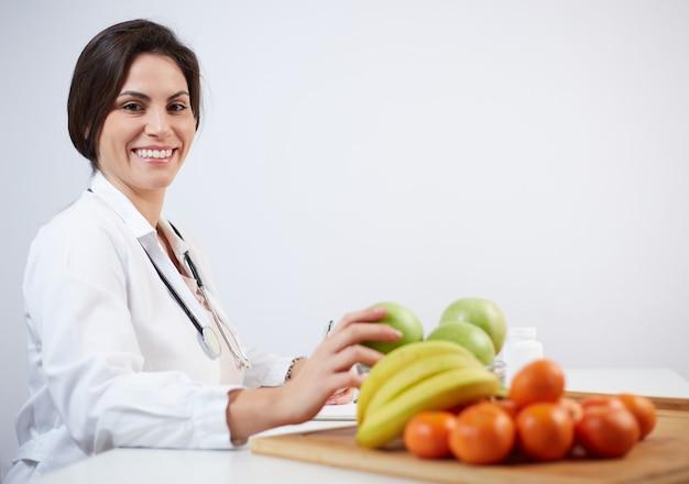 Schöne lächelnde ernährungswissenschaftlerin mit gesunden früchten